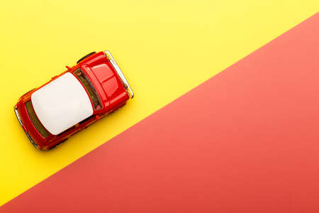 Red small toy car on vibrant yellow background, postcard concept, copy space