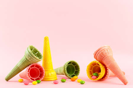 Waffle crispy multi-colored ice cream cones and sweets on pink background, copy space