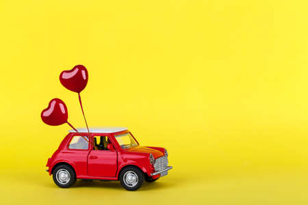 Red small toy car and heart shape ballons on vibrant yellow background, postcard concept, sopy space