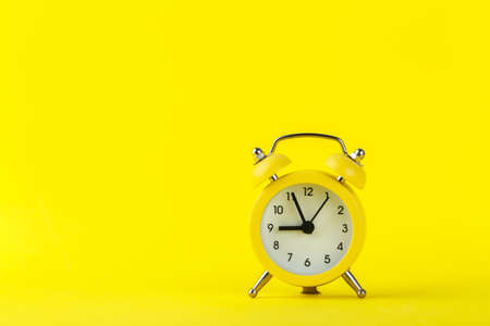 Small alarm clock on yellow background, ringing five minutes to nine, copy space 版權商用圖片