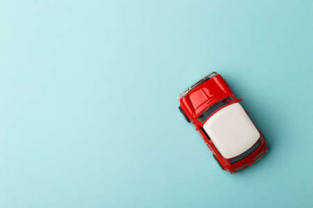 Red small toy car on blue background, postcard concept, copy space 版權商用圖片