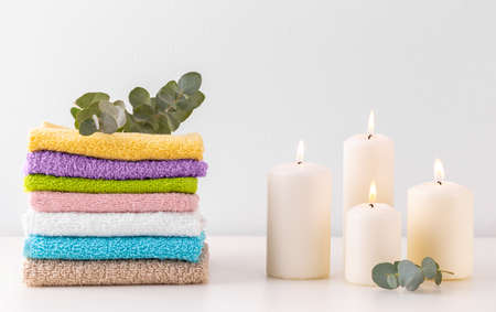 Stack of colorful bath towels, branch of eucalyptus and candles over pastel background