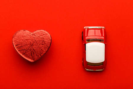 Red small toy car and heart on vibrant background, postcard concept