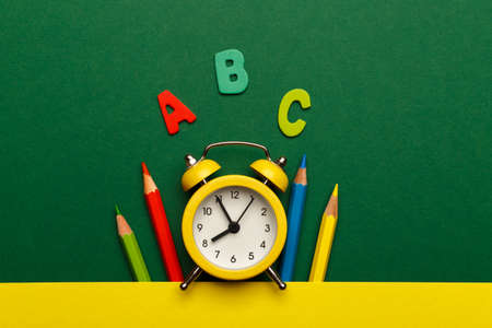 Back to school concept, with colorful wooden letters and yellow alarm clock on green wooden background
