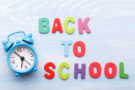 Back to school concept, with colorful wooden letters and alarm clock on blue wooden background