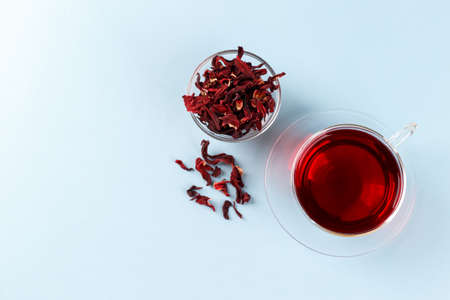 Healthy hibiscus tea in transparent cup on blue background copy space