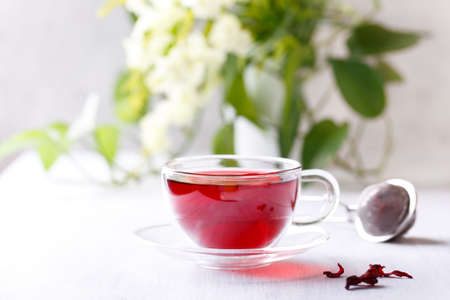 Healthy hibiscus tea in transparent cup on white wooden table in the garden 版權商用圖片