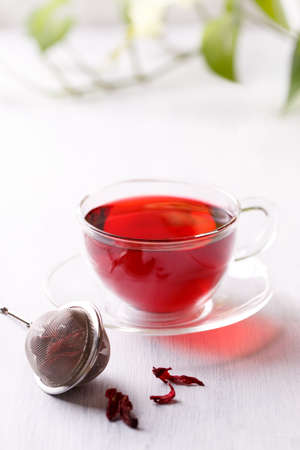 Healthy hibiscus tea in transparent cup on white wooden table in the garden, vertical