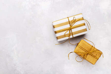 Golden gift boxes on grey stone background, copy space flat lay, Christmas or birthday presents