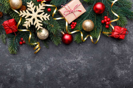 Christmas flat lay with golden gift box, ornaments and fir tree branch on black stone background with copy space