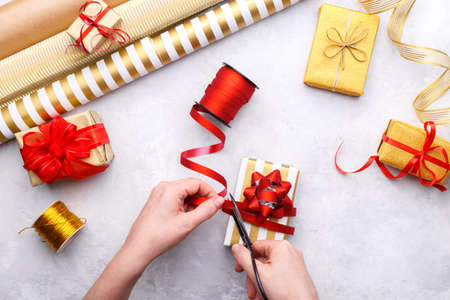 Woman's hands tying up christmas or birthday gift box on grey stone, craft paper gold and red ribbons