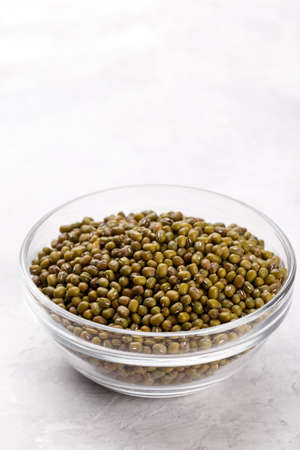 Close up the green mung beans in a bowl on grey stone background