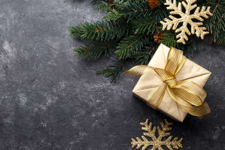 Christmas flat lay with golden gift box and fir tree branch on black stone background with copy space