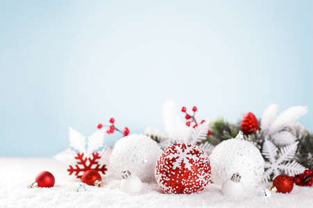 Christmas card template with festive red and white ornaments on the snow, blue background, lights bokeh, copy space
