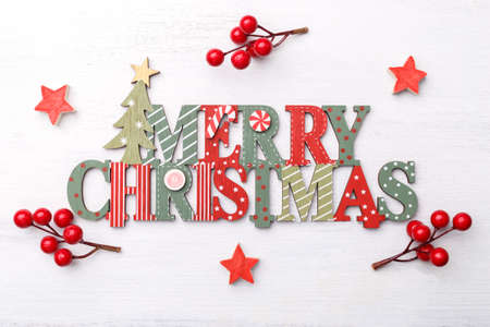 Merry Christmas wooden letters, red berries and stars, festive card template