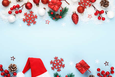 Red Christmas or New year ornaments, berries, stars and snow flakes on blue trendy background with copy space