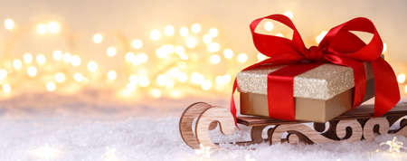 Golden gift box with red ribbon on the sleigh, Christmas or new year greetings card with copy space, banner 免版税图像
