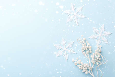 White decorative Christmas or New year ornaments and snow flakes on blue trendy background with copy space Stockfoto