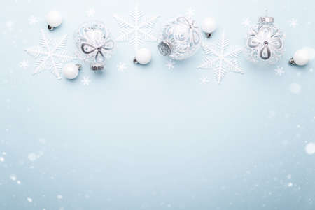 White glass decorative Christmas or New year ornaments and snow flakes on blue trendy background with copy space Stockfoto