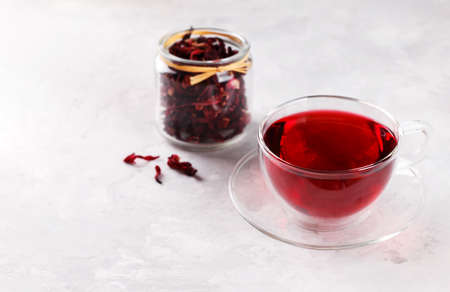 Healthy hibiscus tea in transparent cup on grey stone table with copy space Stockfoto