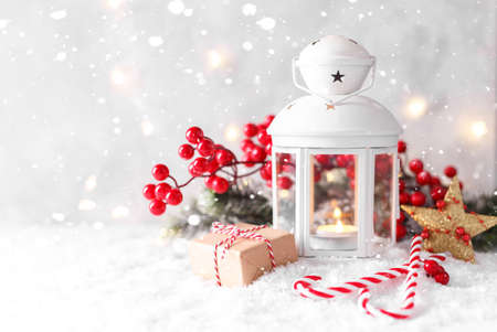 White lantern with candle, red decorations and berries on snow, horizontal Christmas or New year card with copyspace