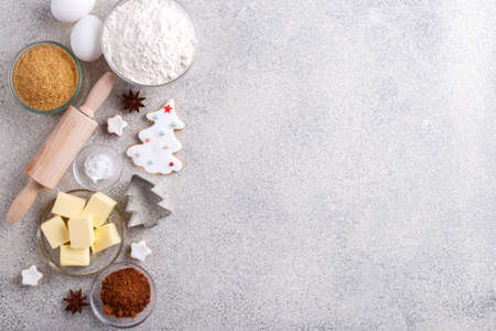 Winter holidays baking background, flour, bakeware, sugar, butter, cookie cutter, eggs, cinnamon and cookies on grey stone kitchen table, view from above with copy space for text Stockfoto