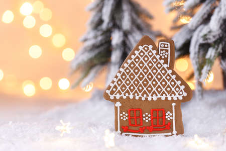 Christmas or New Year homemade gingerbread cookie house shaped, fir tree on the snow, festive greetings card