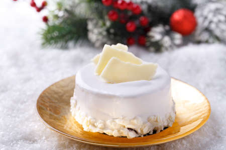 White chocolate Christmas cake on golden plate with festive decorations, horizontal