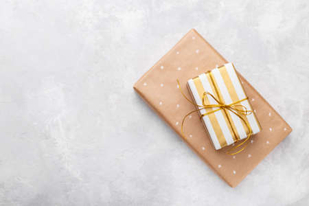Golden gift boxes on grey stone background, copy space flat lay