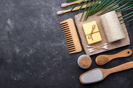Natural bamboo tooth brushes, black dental powder, hair comb, soap and sponge on black