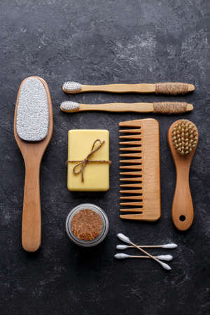 Natural bamboo toothbrushes, black dental powder, hair comb, soap and sponge on black