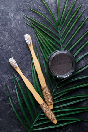 Natural bamboo tooth brushes and black dental powder on black