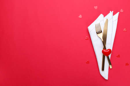 Romantic table setting, gold cutlery on the red table cloth. Stockfoto