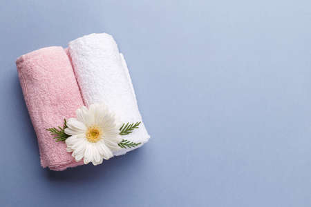 Spa setting, aromatherapy health and wellness on grey background, copy space flat lay, Pink and white towels and flower