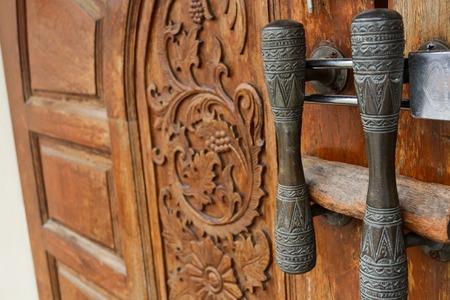 wood door: Old wooden carved door with handle Stock Photo