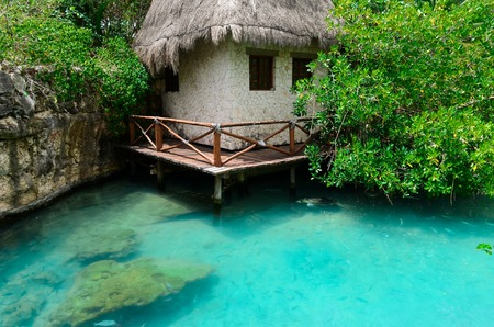 thatched roof: House with thatched roof in a safe Harbor with clear blue waters Stock Photo