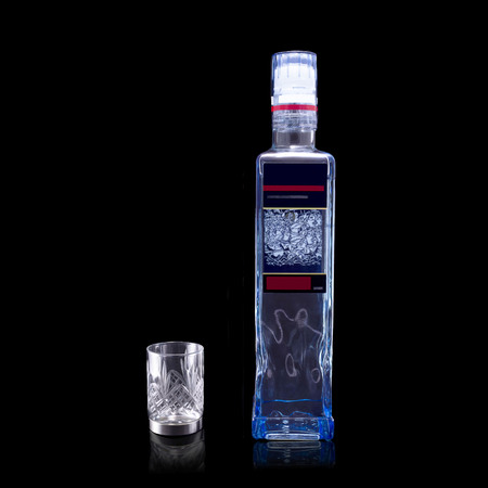 A bottle of vodka and a stack with a pattern on a black background with reflection Stock Photo
