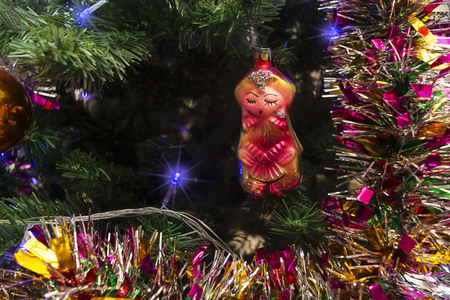 oriental girl: Christmas toys in the form of oriental girl on the background of tinsel and Christmas tree