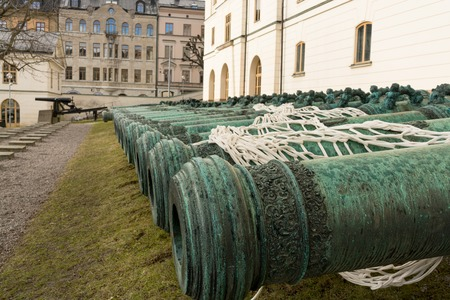 antiquities: Many ancient metal artillery cannons along the white wall Stock Photo