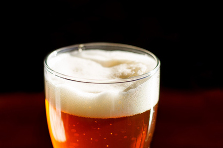 Beer in a glass in the bar with white foam is on the table close up
