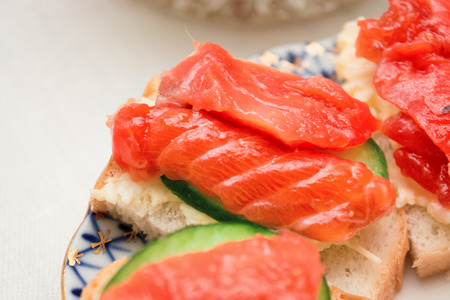 Sandwich with salmon and cucumber on a plate, selective focus Stock Photo