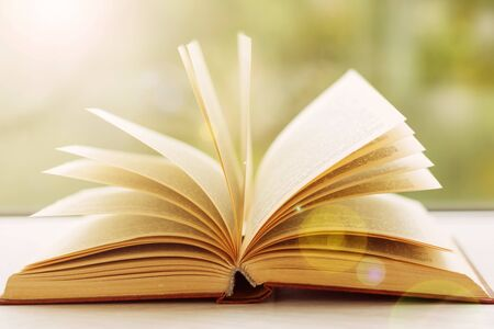 Libro abierto acostado sobre una mesa de madera blanca, iluminada por el sol