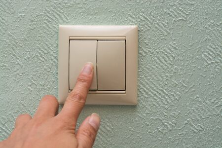 finger presses an electronic light switch on a blue wall background