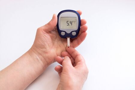 close person checking blood sugar with glucometer and test strip at home
