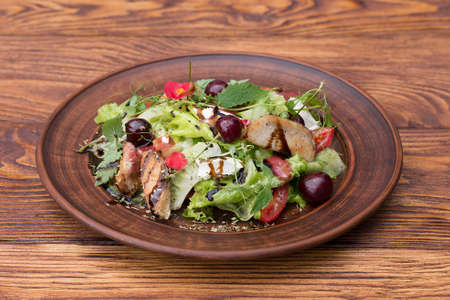 salad with turkey, cherry, lettuce and tomatoes on a plate with a wooden background Banque d'images