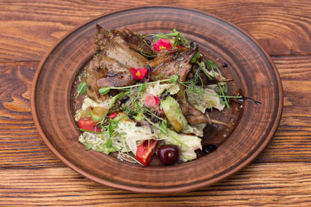 salad with quail, cherries, lettuce, cheese and tomatoes on a plate with a wooden background