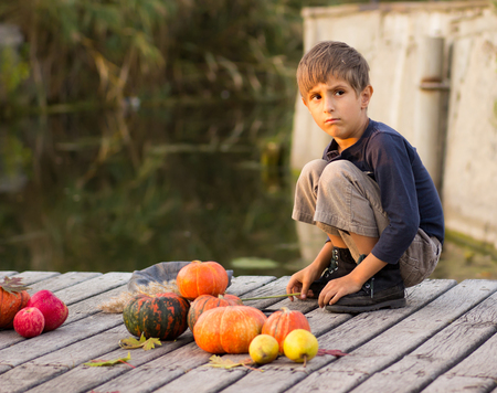 children painting: Ordinary boy sitting with Halloween pumpkins on the river bank Stock Photo