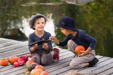 children painting: Laughing children paint small Halloween pumpkins on the river bank Stock Photo