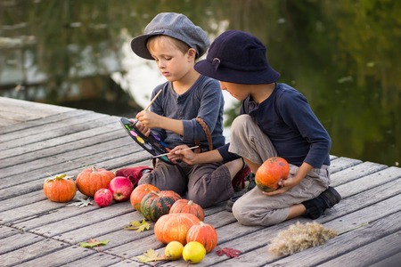 children painting: Ordinary children paint small Halloween pumpkins on the river bank Stock Photo