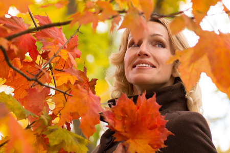 Laughing young woman dreams under an autumn tree Stock Photo